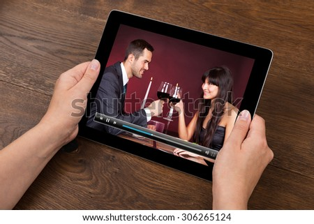 Close-up Of Person Hands With Digital Tablet Showing Video At Desk