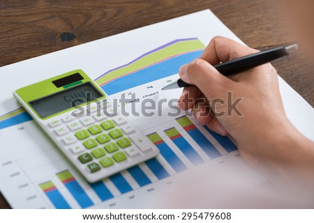 Close-up Of Person Hands With Graph And Calculator At Desk - stock photo