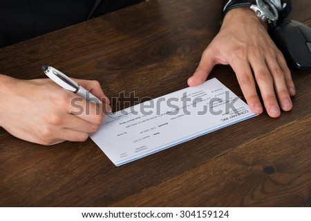 Close-up Of Person Hands With Pen Signing Cheque At Desk - stock photo