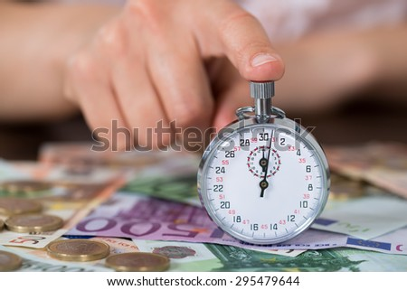 Close-up Of Person Hands With Stopwatch And Coins Over Euro Banknote - stock photo