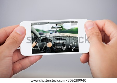 Close-up Of Person Hands With White Mobile Phone Playing Car Game - stock photo