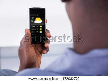 Close-up Of Person Holding Mobile Phone Showing Weather - stock photo