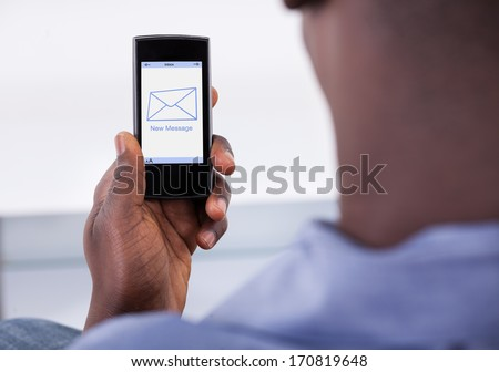 Close-up Of Person Holding Mobile Phone With One New Message Showing On A Screen - stock photo