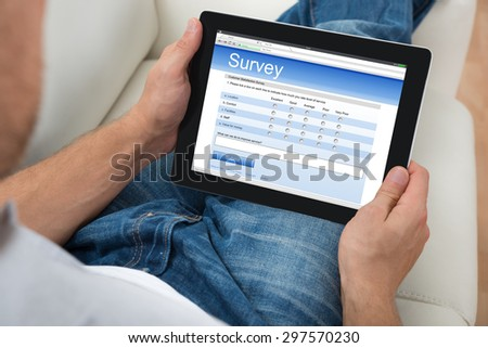 Close-up Of Person On Sofa With Digital Tablet Showing Survey Form - stock photo