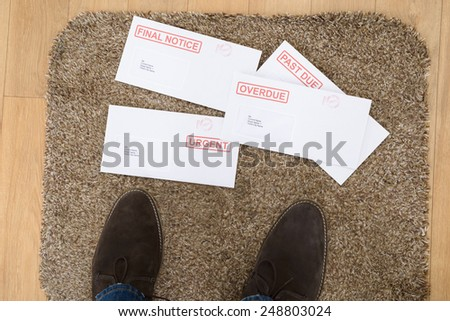 Close-up Of Person's Feet And Important Letters On Doormat - stock photo