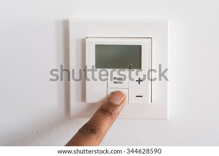 Close-up Of Person's Finger Adjusting Room Temperature On Digital Thermostat - stock photo
