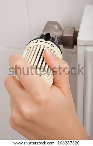 Close-up Of Person's Hand Adjusting Temperature By Thermostat - stock photo