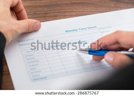 Close-up Of Person's Hand Filling Blank Weekly Time Sheet With Pen