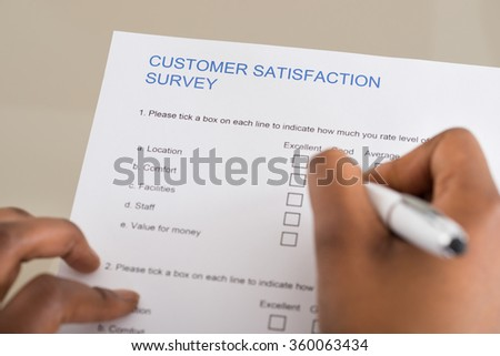 Close-up Of Person's Hand Filling Customer Satisfaction Form - stock photo