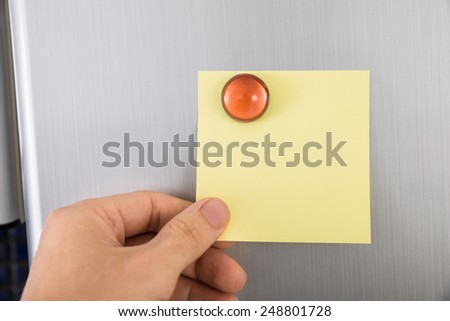 Close-up Of Person's Hand Holding Blank Yellow Note Sticked On Fridge Door - stock photo