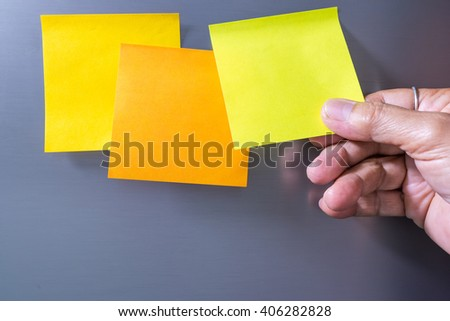 Close-up Of Person's Hand Holding Blank Yellow Note Sticked On Fridge Door