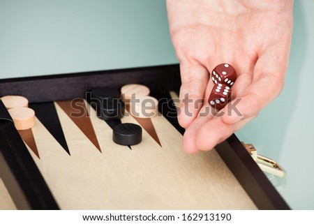 Close-up Of Person's Hand Holding Dice Playing Backgammon - stock photo