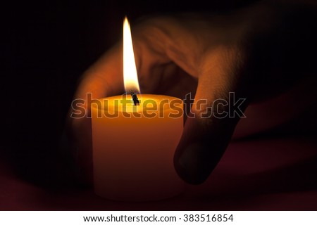 Close-up of person's hand holding illuminated candle.