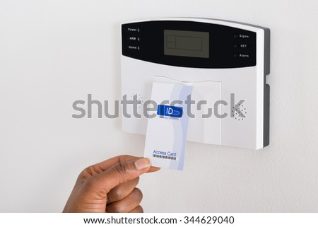 Close-up Of Person's Hand Holding Keycard To Open Door - stock photo