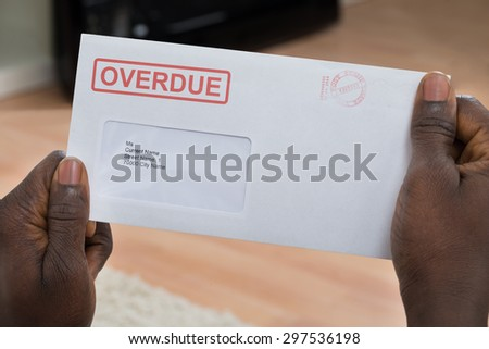 Close-up Of Person's Hand Holding Overdue Notice - stock photo