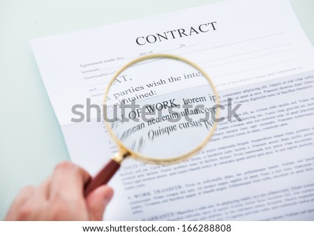 Close-up Of Person's Hand Looking At Contract Through Magnifying Glass - stock photo