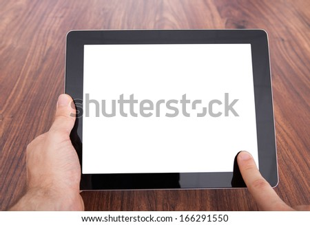 Close-up Of Person's Hand On Wooden Table Holding Digital Tablet - stock photo