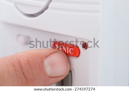 Close-up Of Person's Hand Pressing Panic Button - stock photo