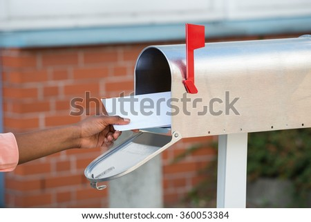 Close-up Of Person's Hand Putting Letters In Mailbox - stock photo