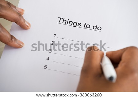Close-up Of Person's Hand Writing Things To Do List On Paper - stock photo