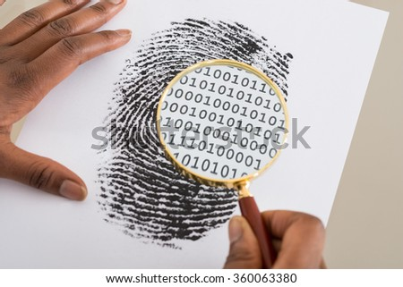 Close-up Of Person Using Magnifying Glass To Check Binary Code Within Finger Print - stock photo