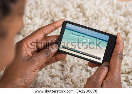 Close-up Of Person Watching Video On Mobile Phone - stock photo