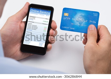 Close-up Of Person With Credit Card And Mobile Phone Doing Online Banking - stock photo