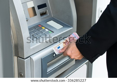 Close-up Of Person Withdrawing Money From Atm Machine