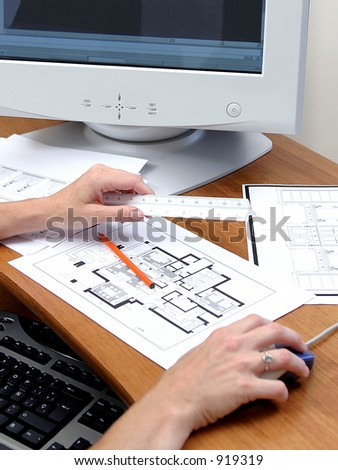 Close up of person working on a computer or PC Plans of a house a ruler and pencil are on the wooden desk - stock photo
