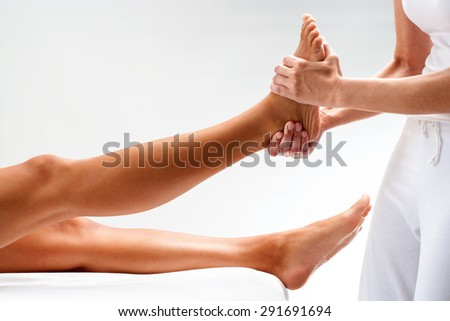 Close up of physiotherapist massaging female foot. Isolated on light background. - stock photo