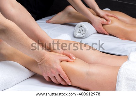 Close up of physiotherapists massaging couple together in spa.