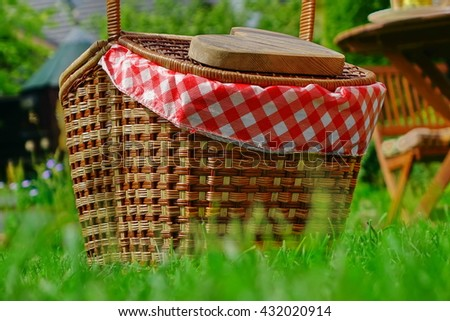 Close-up Of Picnic Basket  Or Hamper With Checkered Cloth On The Backyard Lawn. Wooden Heart On The Basket Cover - stock photo