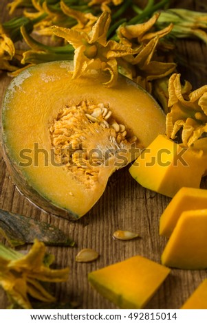 Close up of Pieces of cut squash and edible squash flowers on brown, wooden table