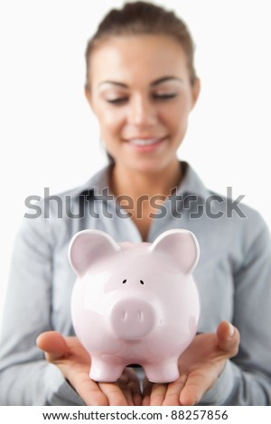 Close up of piggy bank being held by female bank assistant against a white background