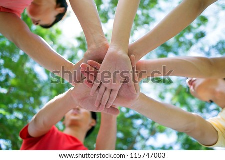 Close-up of pile of hands of teenagers