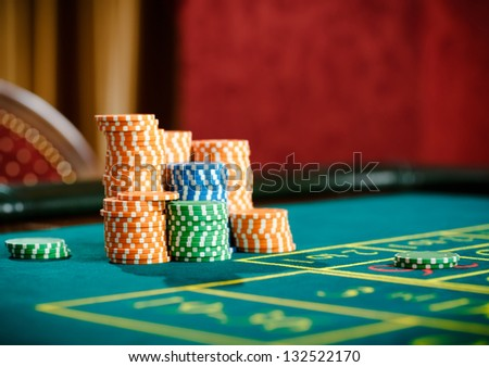 Close up of piles of chips on the roulette table. Symbol of addiction to the gambling - stock photo
