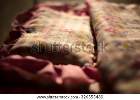 Close up of pillow and blanket with pink flower ornament on the bed in morning light - stock photo