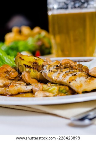 Close Up of Pineapple Cashew Chicken Dish on Plate Served with Glass of Beer in Restaurant - stock photo