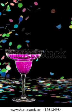 Close-up of pink alcoholic drink and streamers against black background - stock photo
