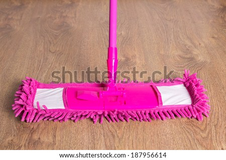 close up of pink cleaning mop on wooden parquet floor - stock photo