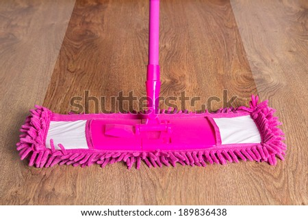 close up of pink cleaning mop on wooden parquet floor - before after - stock photo