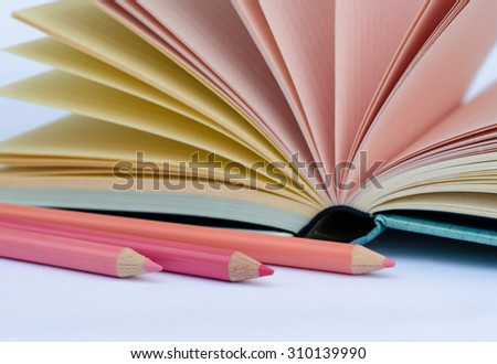 Close up of pink color pencils and opened colorful pages diary note book on white background. - stock photo
