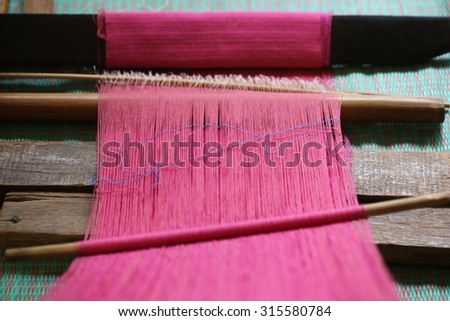 Close up of pink silk weaving on loom, cotton on the manual wood loom in Asian traditional culture and woman lifestyle,Weaving shuttle on the warp. fashion fabric factory and business in Thailand.hand - stock photo