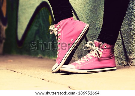 Close up of pink sneakers worn by a teenager. Grunge graffiti wall, concepts of teen rebel, problems of the youth, drugs, alcohol. - stock photo