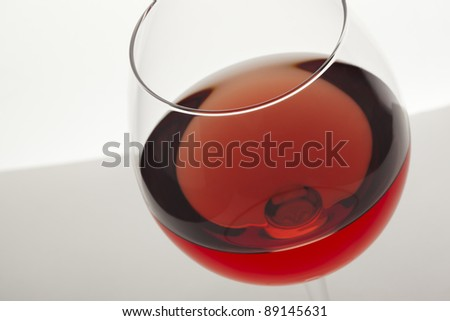 Close up of pink wine glass with white and grey background.