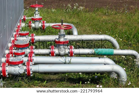 close-up of pipes and valves in a field on a background of grass in the summer - stock photo