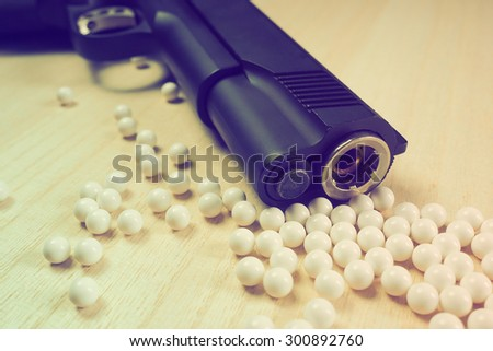 Close up of pistol. 11 mm or 0.45 and BB gun bullet. Toned image. - stock photo