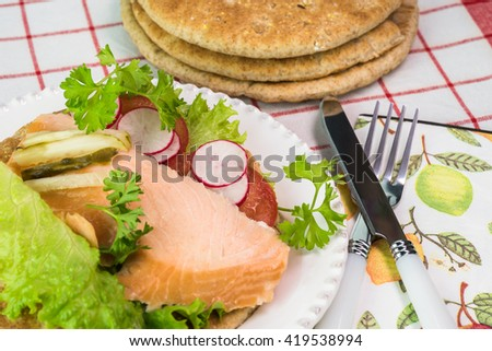 Close up of pita sandwich with hot smoked salmon and vegetables on a white plate.