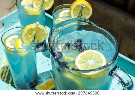 Close up of pitcher and glasses filled with blueberry lemonade with fresh lemons and blueberries and yellow swirled straws sitting in blue drink tray - stock photo