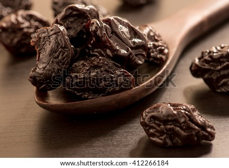 Close up of pitted prunes on black color wooden spoon - stock photo